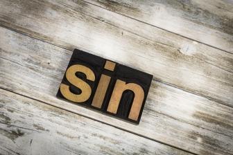 Sin Letterpress Word on Wooden Background