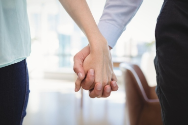 Mid section of couple standing with hand in hand
