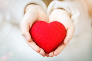 Red heart in hands of the little girl. Symbol of love and family.Valentines day card. Mother's day. Backgrounds for social posters. Selective focus