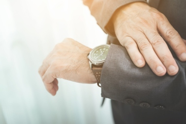 Close up of businessman in grey suit looking watch.